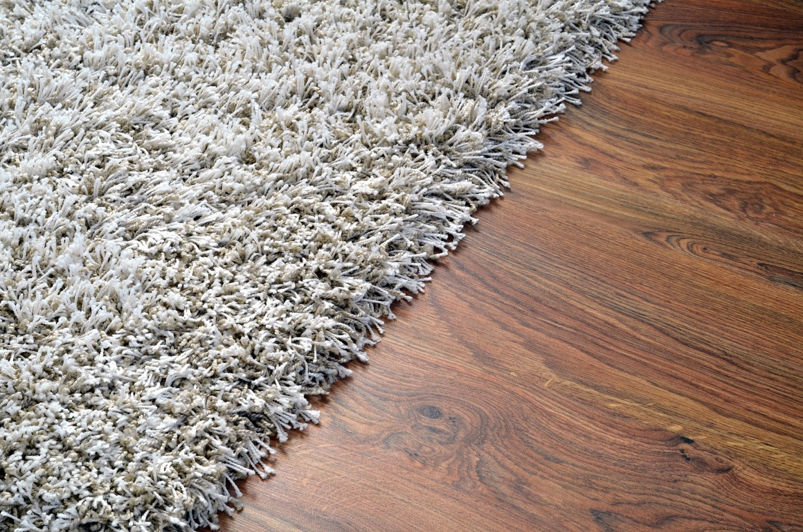 White shaggy carpet on brown wooden floor
